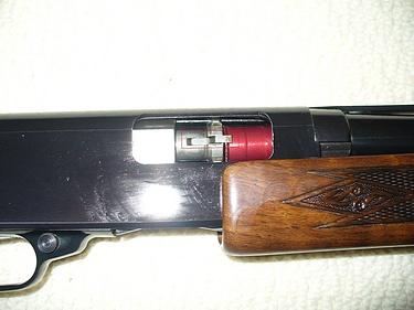 shotgun, action partially open with dummy round hooked on extractor